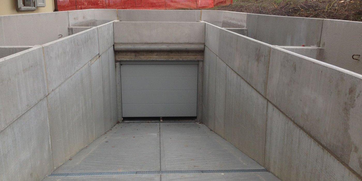 una discesa di un parcheggio sotterraneo con una porta grigia