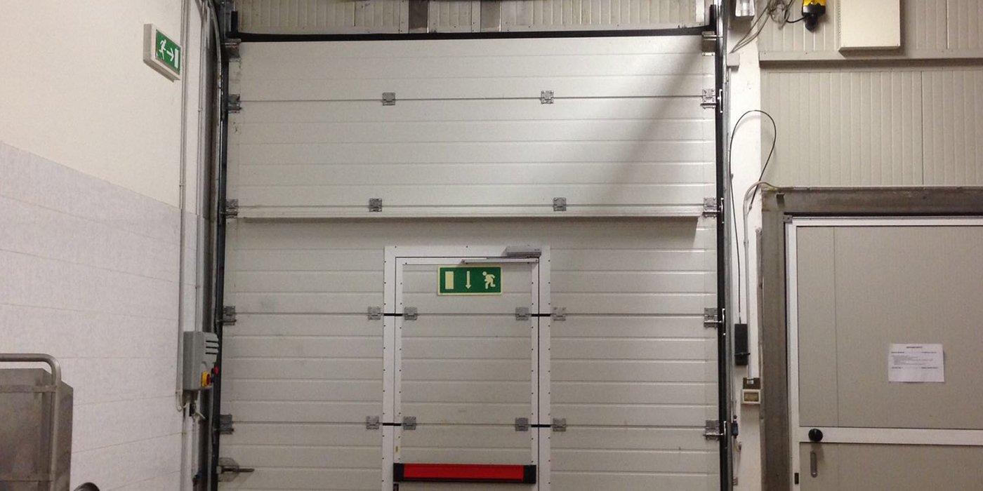 una porta di emergenza color bianco con maniglione antipanico rosso