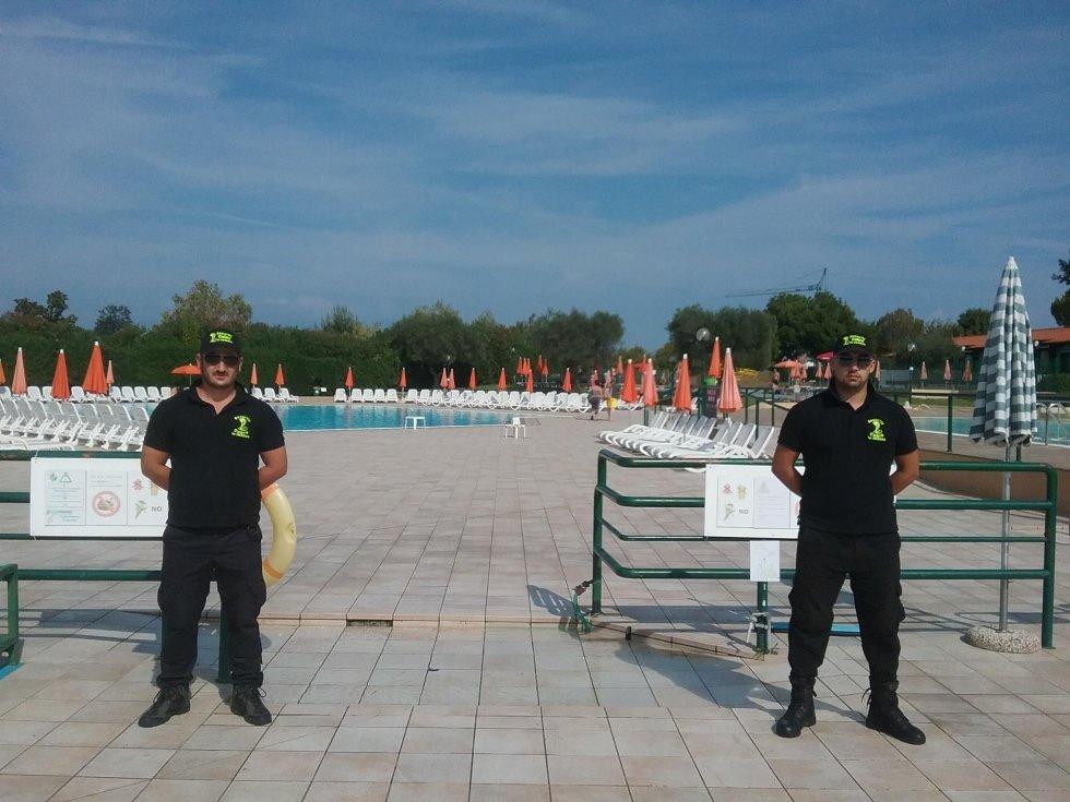 due guardie di sicurezza e vista di una piscina e degli ombrelloni