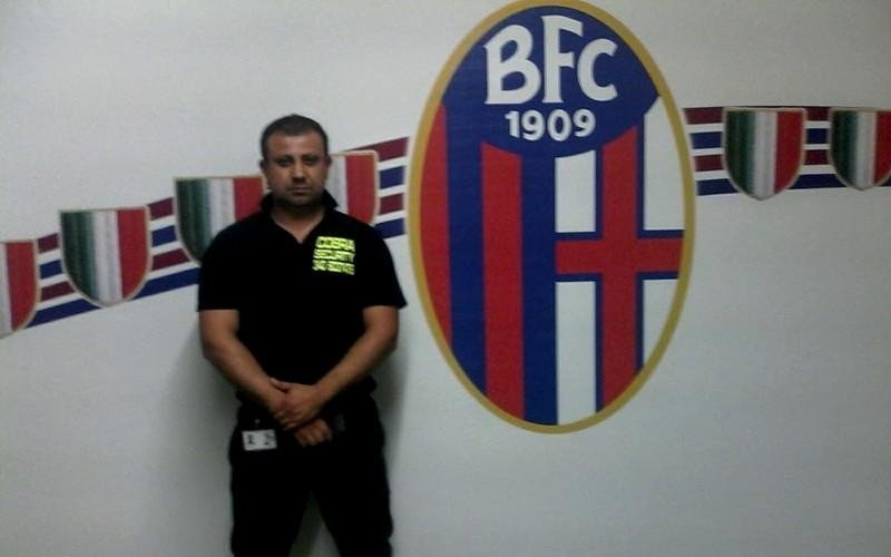una guardia di sicurezza vicino a un muro con dipinto lo stemma della squadra di calcio Bologna F.C