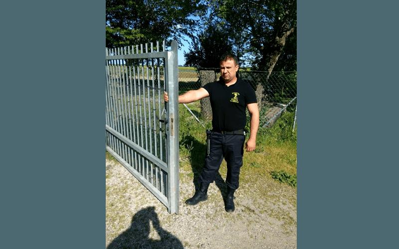 una guardia di sicurezza appoggiata a un cancello