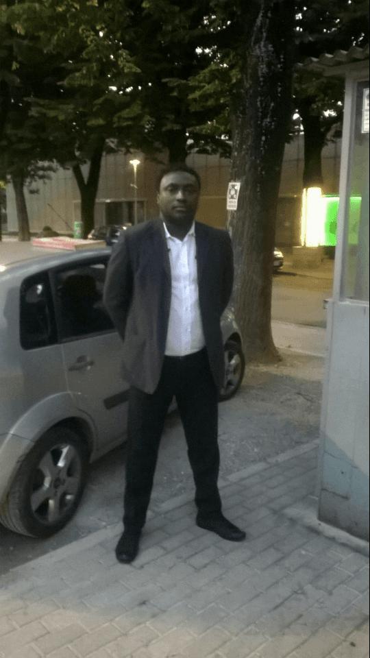 un uomo di colore vestito formale in posa per una foto