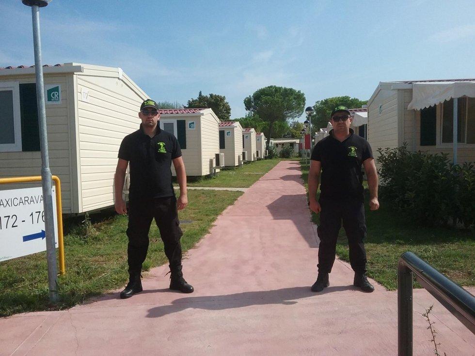 due guardie di sicurezza e dietro un campo da tennis