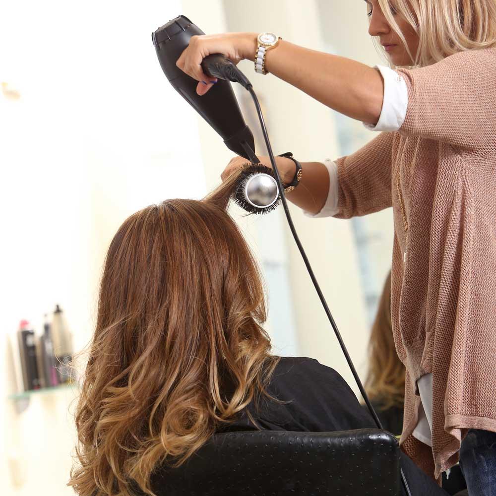 A stylist curls a woman's hair