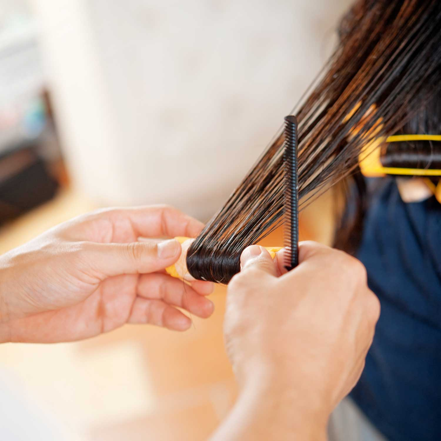 A stylist uses curlers to added bounce to a woman's hair