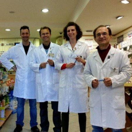 quattro uomini e una donna con un camice bianco in una farmacia