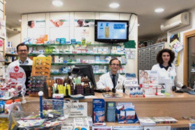interno di una farmacia con due uomini e una donna con un  camice bianco