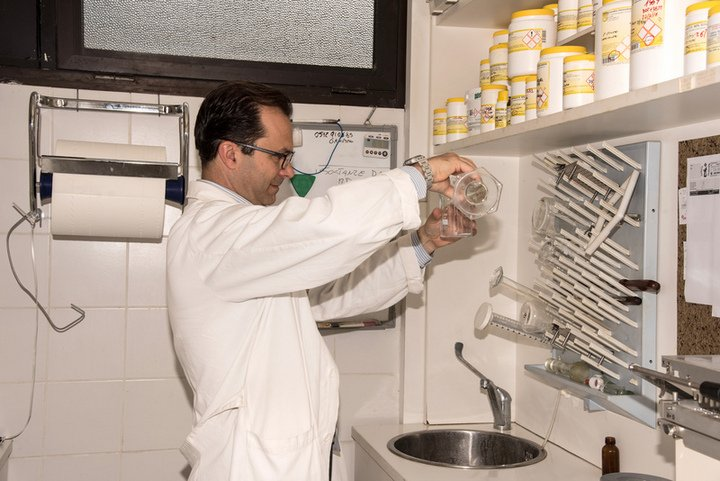 un uomo con un camice bianco in un laboratorio e vista delle mensole con dei barattoli