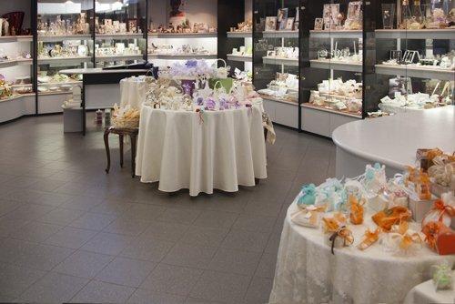 vista interna di un negozio di bomboniere con confetti e decorazione sul tavoli