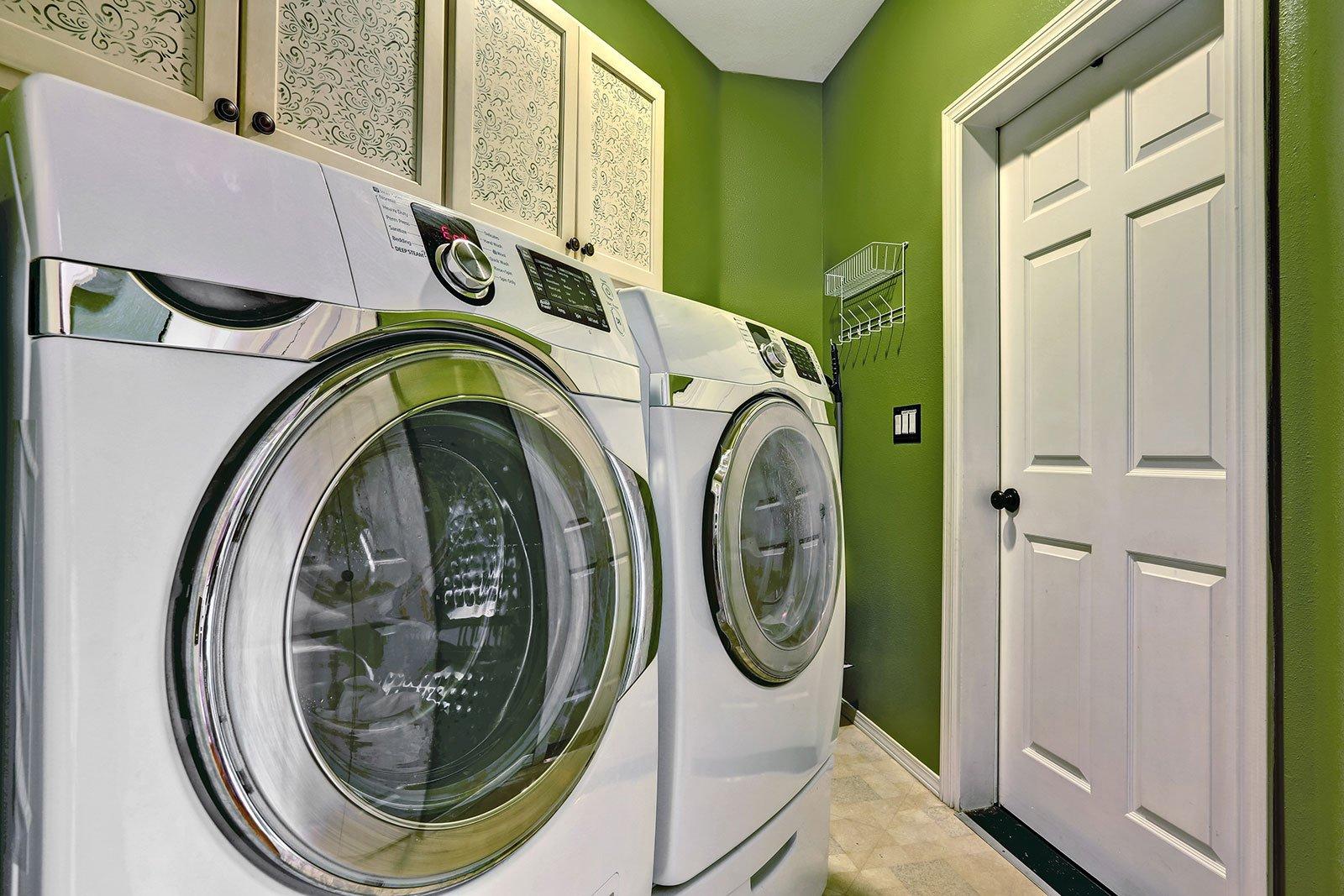 interni lavanderia con elettrodomestici moderni e armadi.