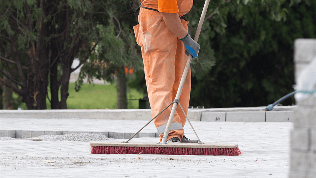 Construction worker sweeping on the building site