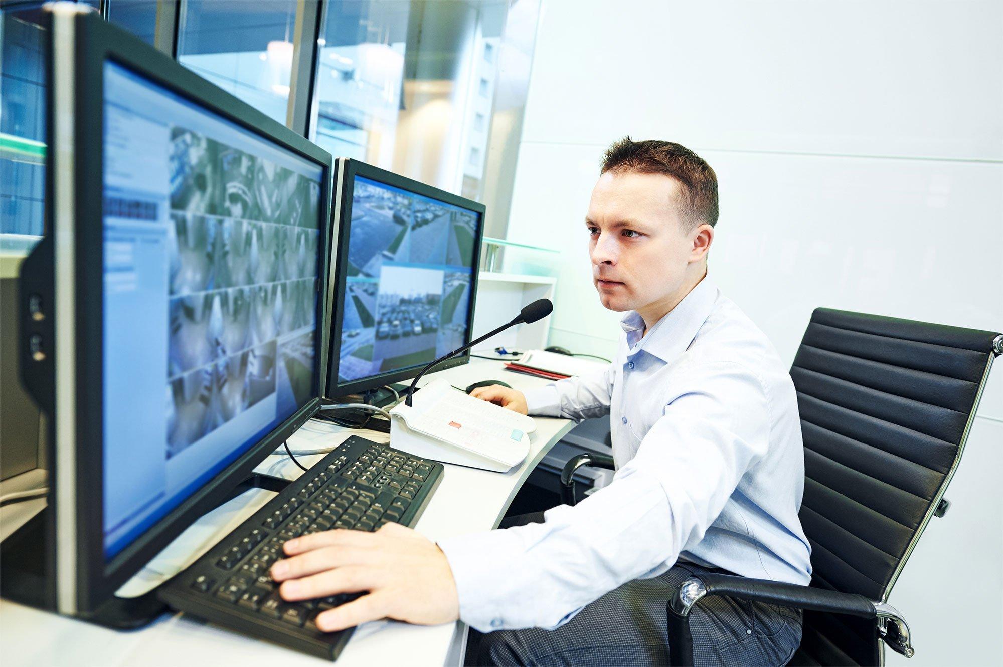man watching security monitors