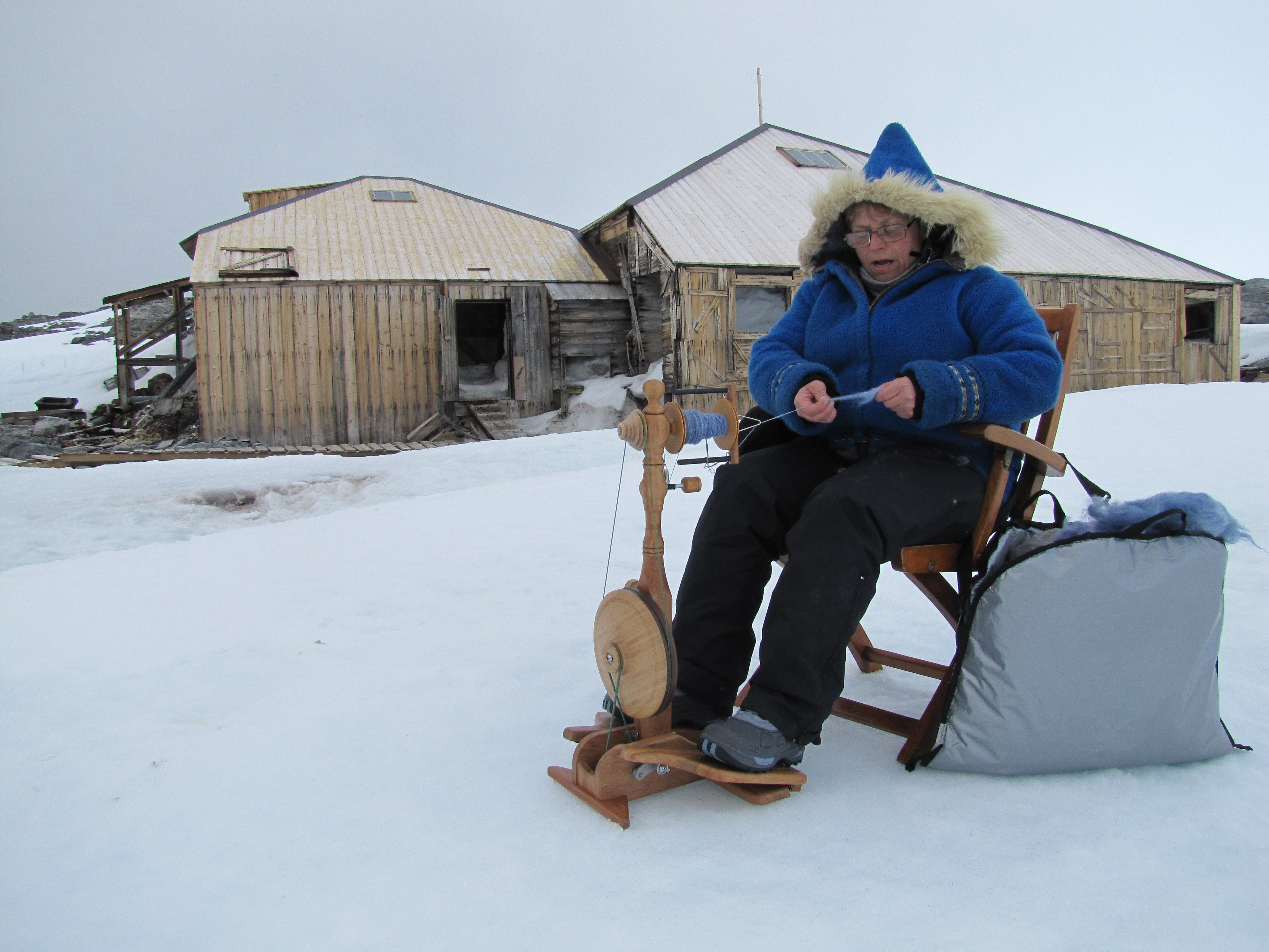 Old woman spinning yarn in snow