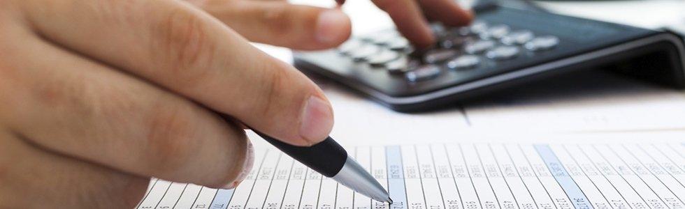 una mano con una penna e una calcolatrice