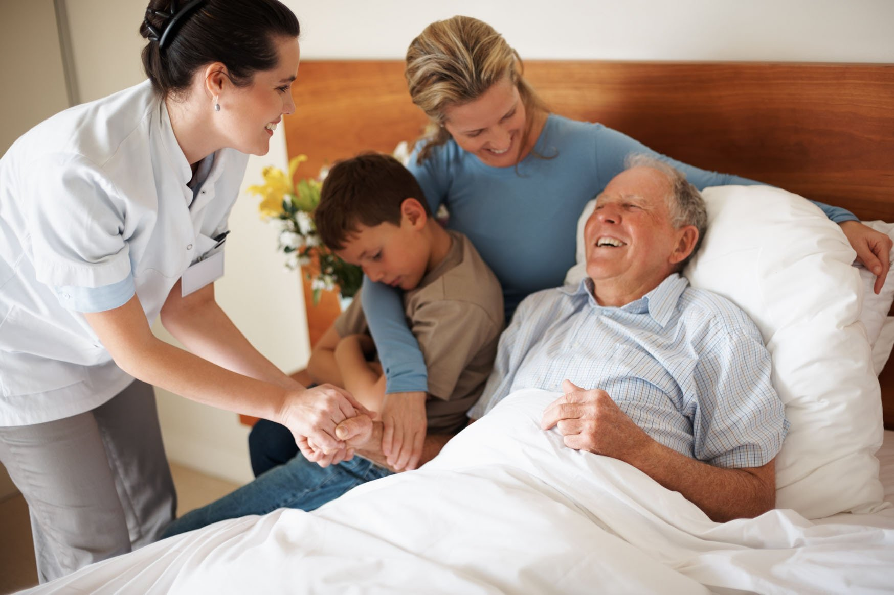 Senior man on bed with daughters holding his hand