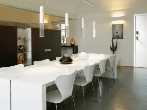 vista interna di una sala da pranzo con tavolo e sedie bianche e arredamento