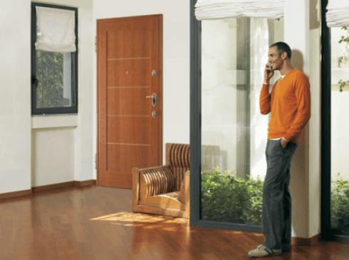 un uomo mentre parla al telefono in dentro di una stanza con porta blindata in legno, pavimento in legno e arredamento di una casa