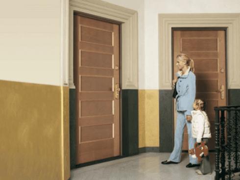 vista esterna di una casa con porte in legno moderne e una donna con bambina
