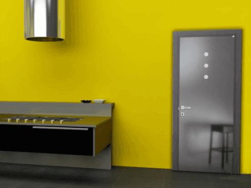 vista interna di una casa con porta in legno e parete gialla