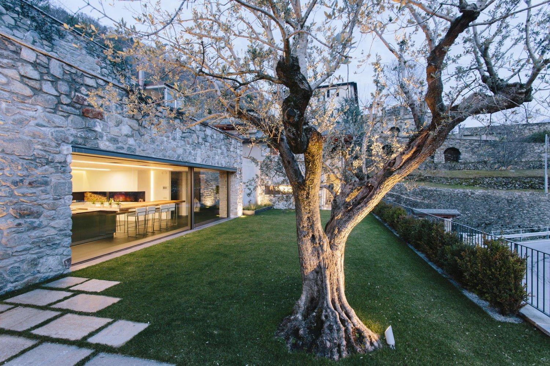 vista laterale di un edificio in pietra con giardino e un grande albero