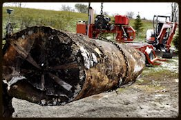 Sawmill on wheels lifting large log.