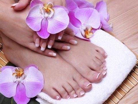 mani e piedi sopra un asciugamano con dei fiori sopra