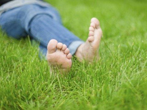persona stesa sull`erba con piedi nudi e gambe incrociate