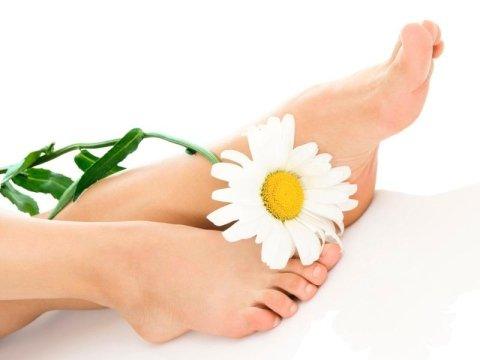 piedi curati di una donna con in mezzo una margherita