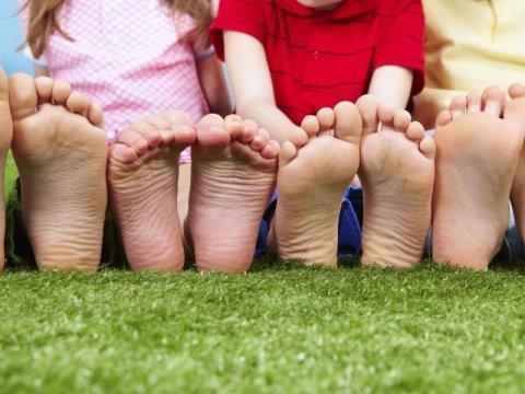 fila di piedi di bambini seduti su un prato