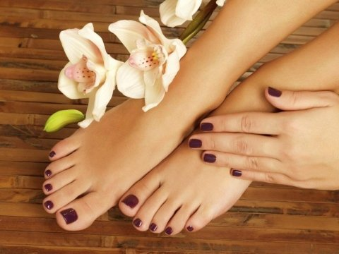piedi e mani curati di una donna con smalto viola sulle unghie