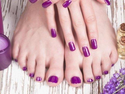 mani e piedi di una donna con smalto viola sulle unghie