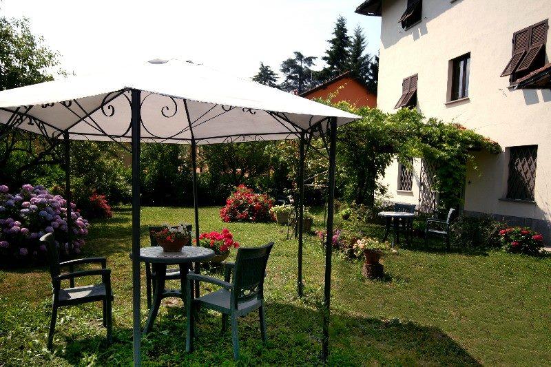 un giardino con un gazebo e dei tavoli