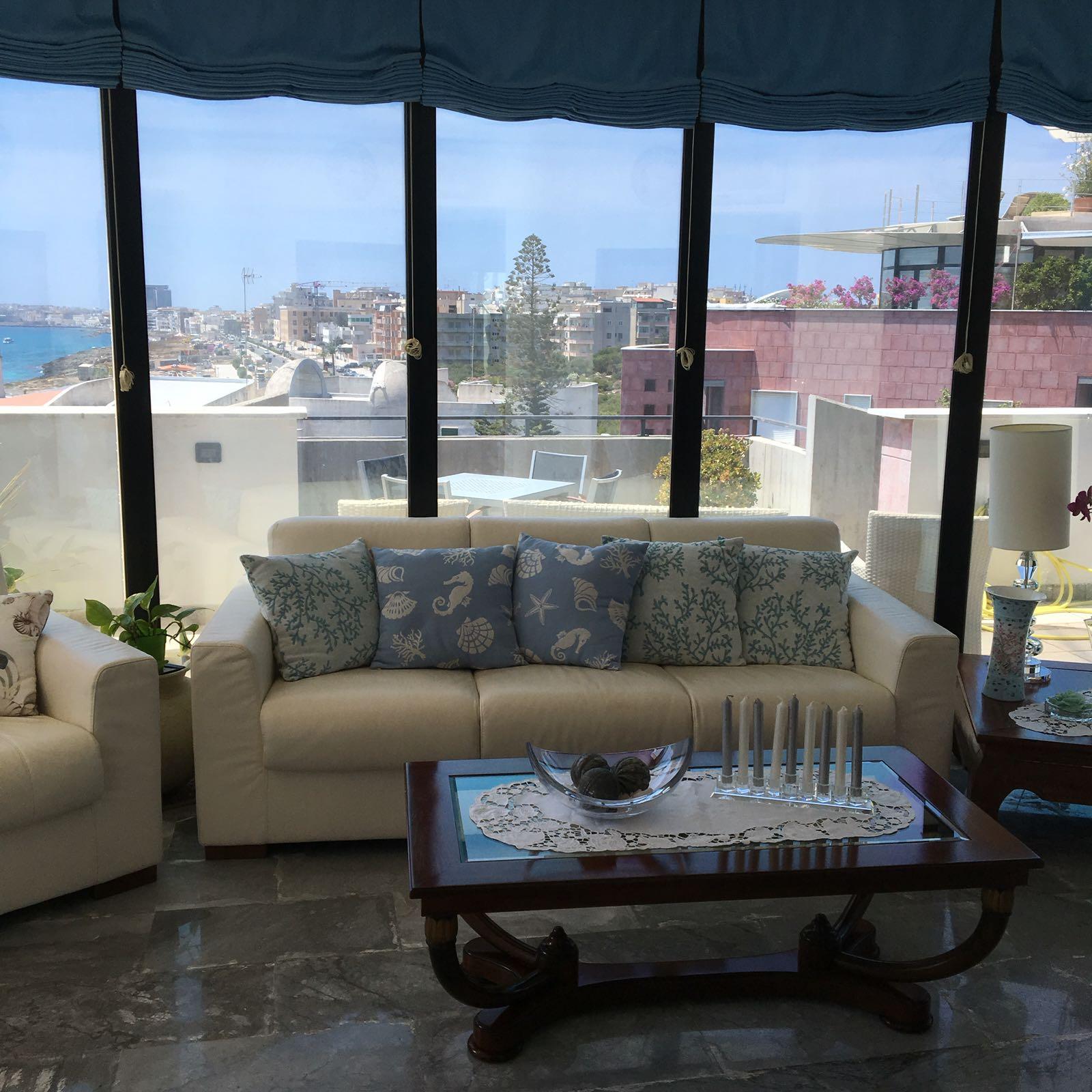 Soggiorno con divano bianco e grande vetrata