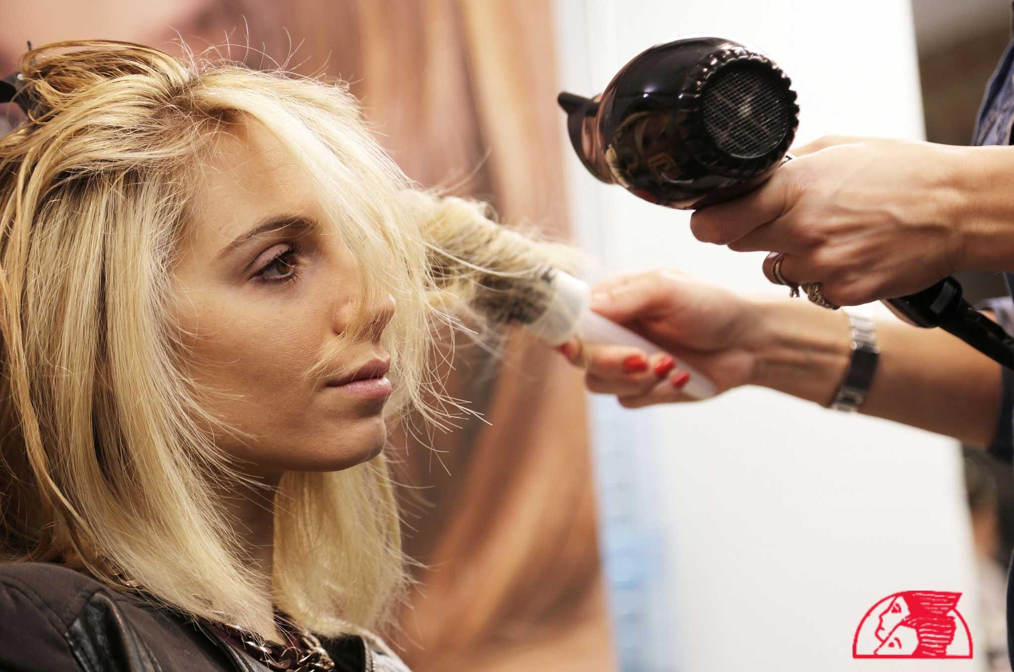 una parrucchiere che sistema i capelli di una ragazza bionda