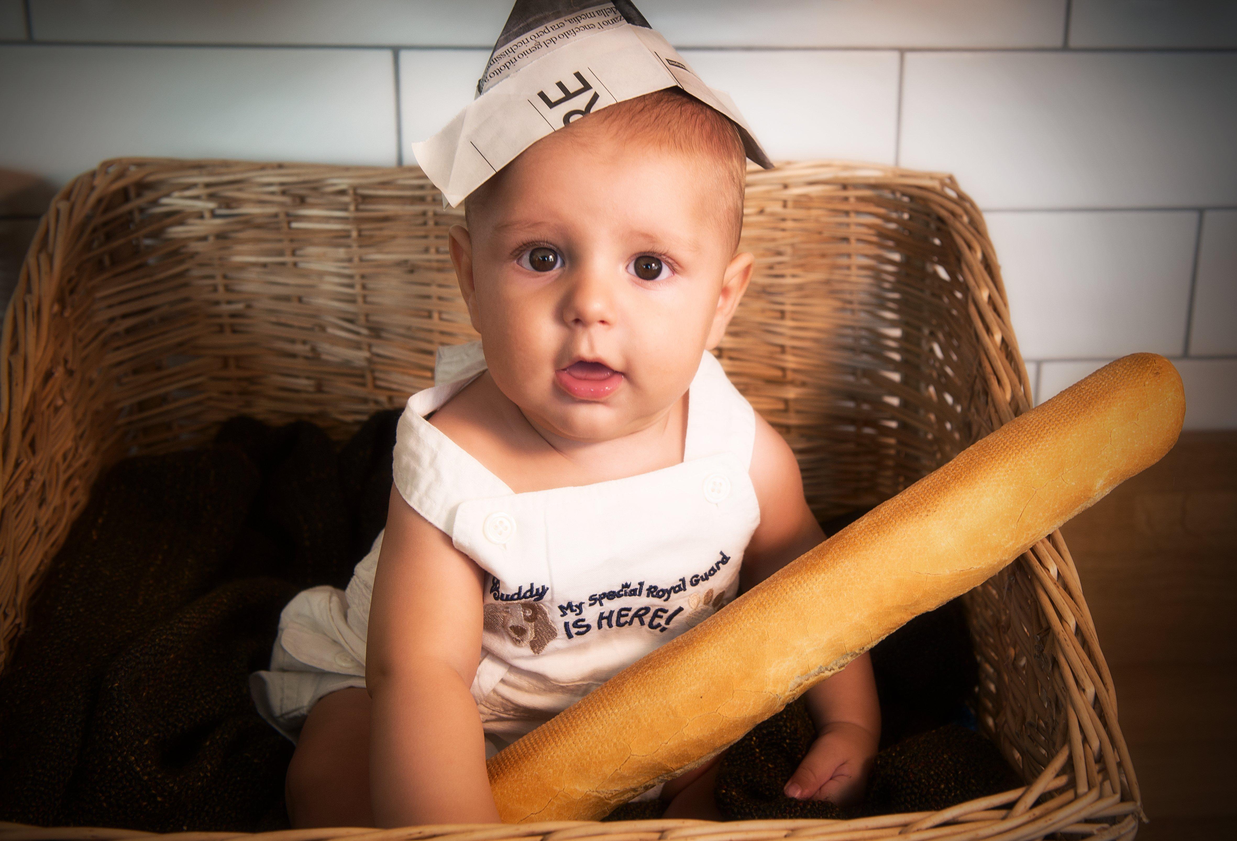 un neonato con un baguette seduto in un cestino