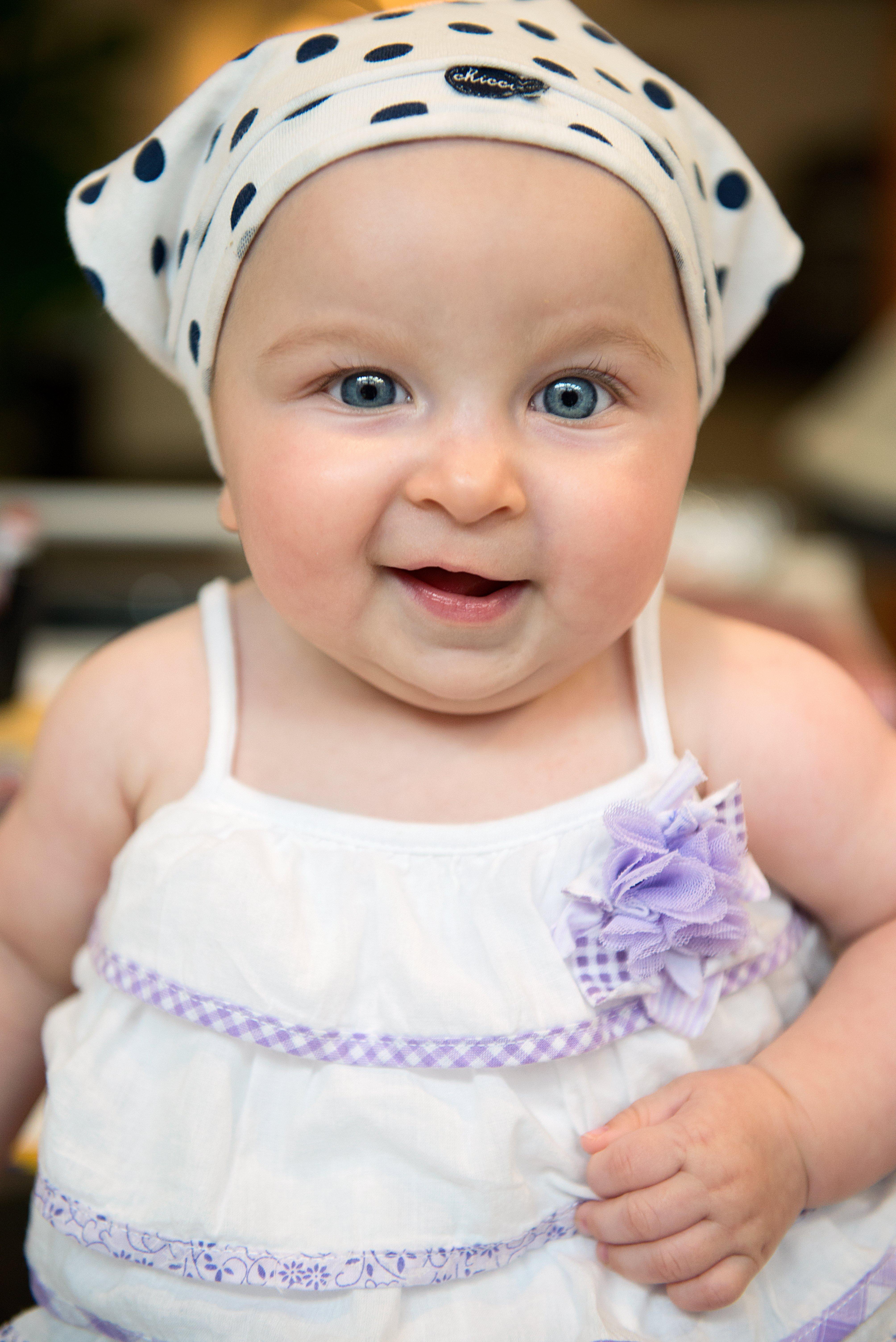 una bambina con un vestito di color bianco e lilla