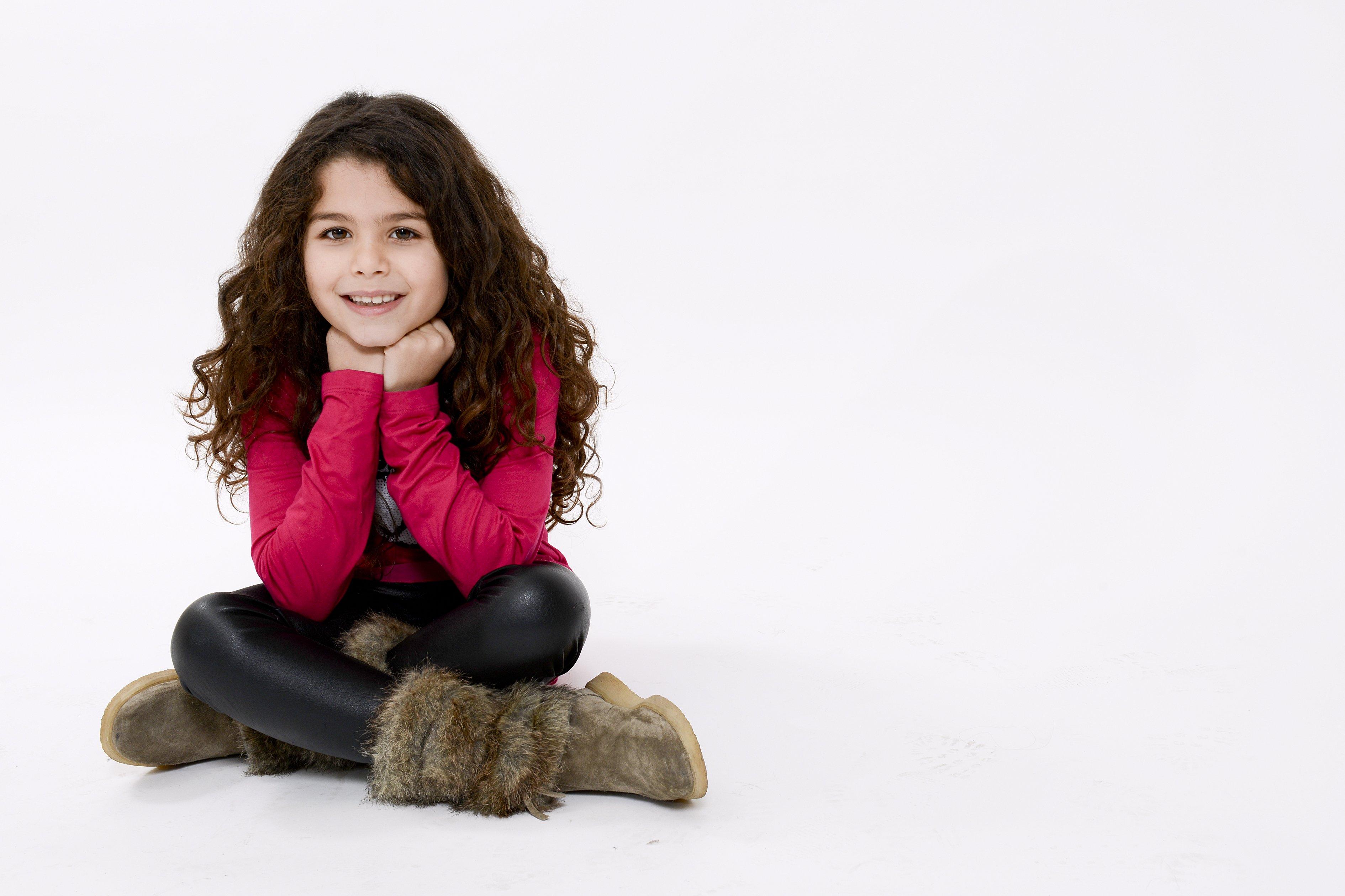 una bambina seduta con una maglia rossa