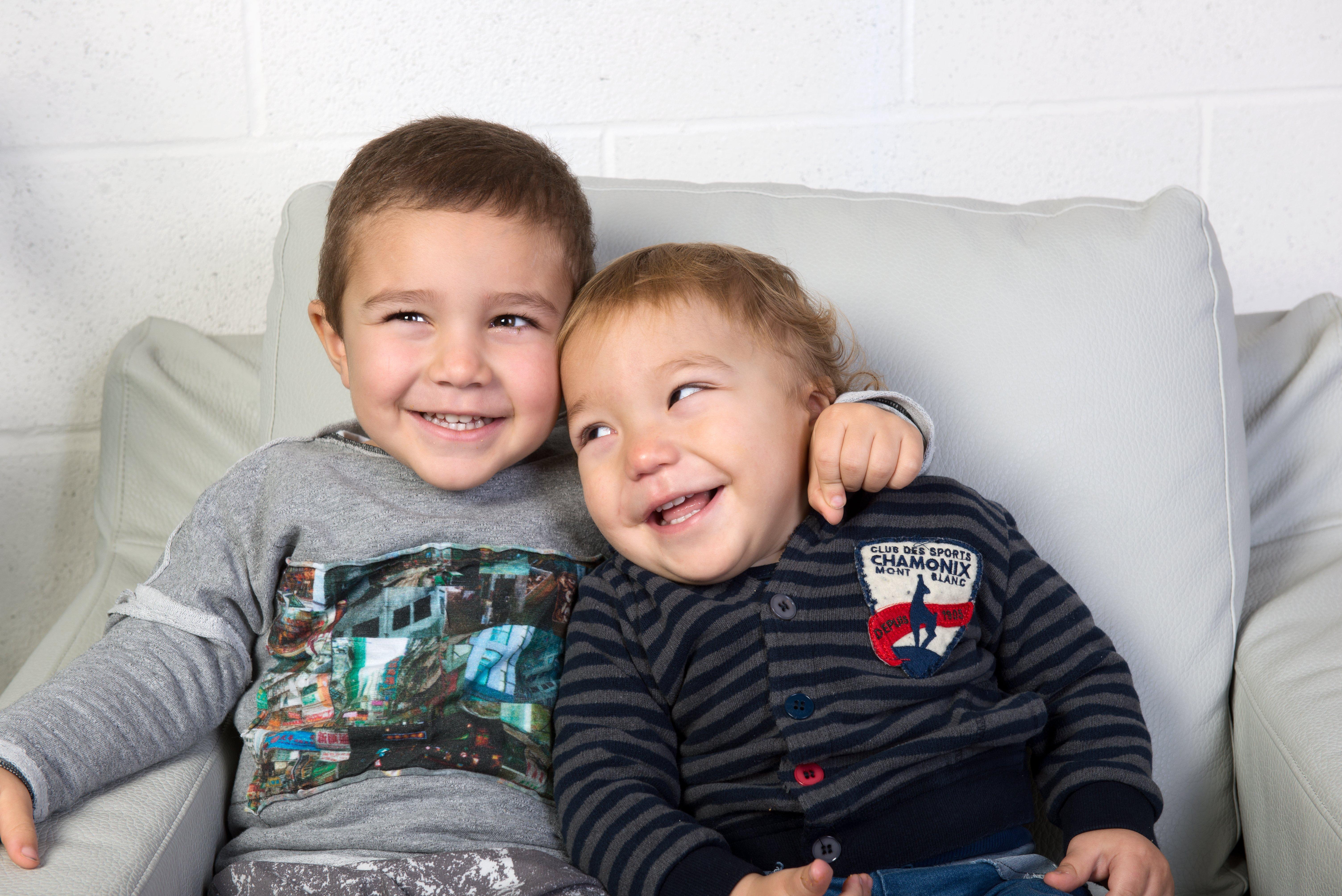 due bambini abbracciati e seduti su una poltrona