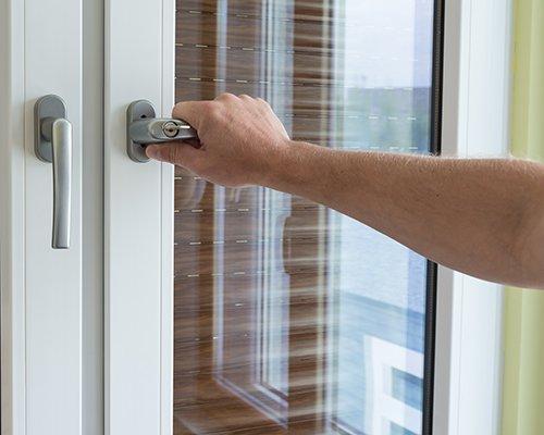 Mano sulla maniglia di una porta in PVC a Campagna Lupia
