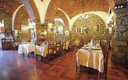 i tavoli all'interno del ristorante apparecchiati per un ricevimento