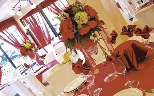 un tavolo apparecchiato con una tovaglia rossa e un vaso di fiori