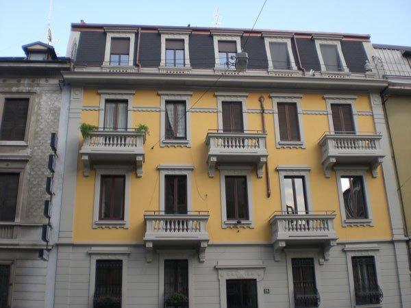 vista esterna di un edificio giallo con balconi