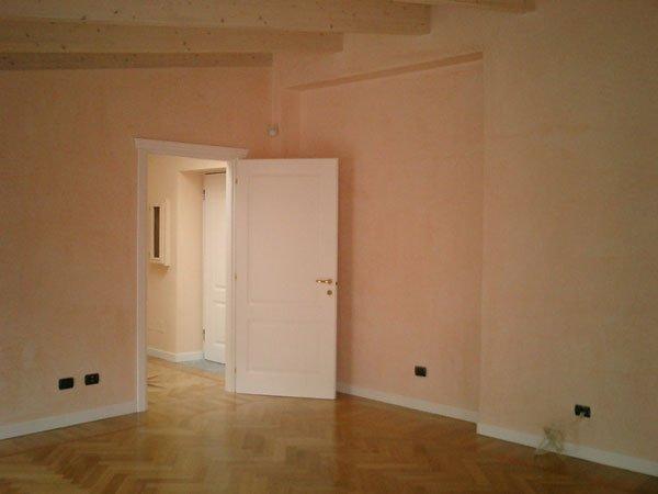 vista interna di una casa con pavimento in legno e porta bianca