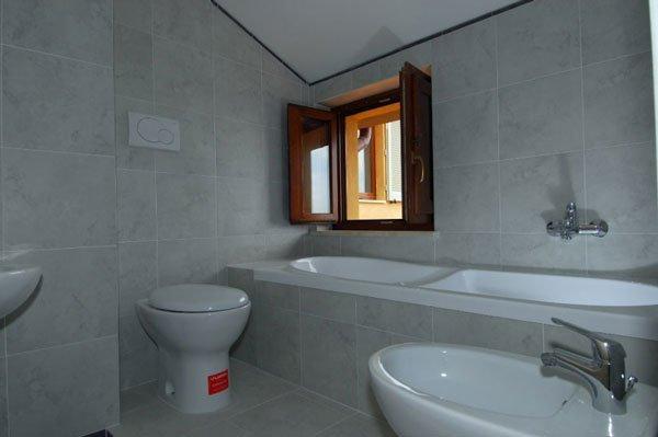 lavabi con rubinetto in acciaio, specchio e una finestra aperta