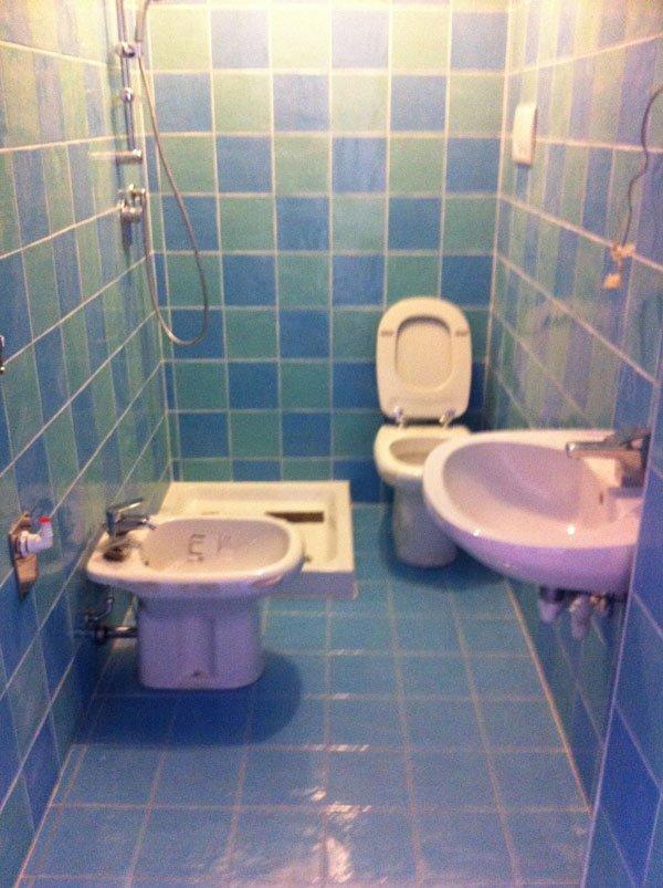 bagno con lavabo, specchio, bide e parete in piastrelle