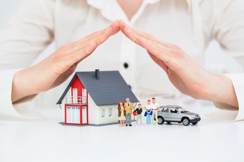 Mani tese a formare un tetto e sotto un modellino di una casa degli omini giocattolo e un modellino di una macchina - Agenzia Generale Celico Tua Assicurazioni