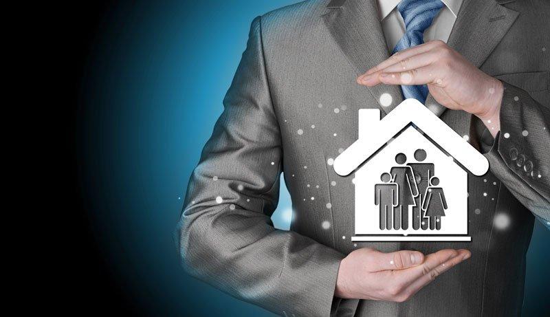 Un uomo con un completo grigio mostra un'immagine con una casa con degli omini che formano una famiglia - Agenzia Generale Celico Tua Assicurazione