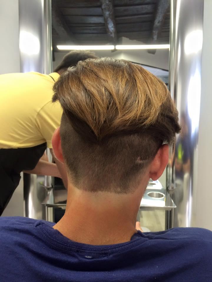 uomo con capelli castani rasati sotto e lunghi sopra