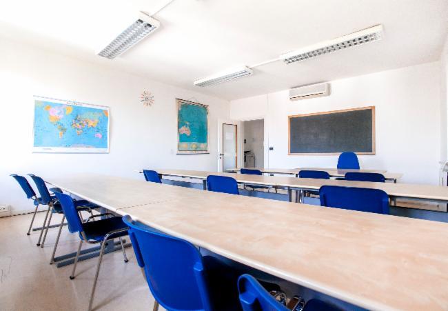 dei banchi lunghi con delle sedie blu in un aula