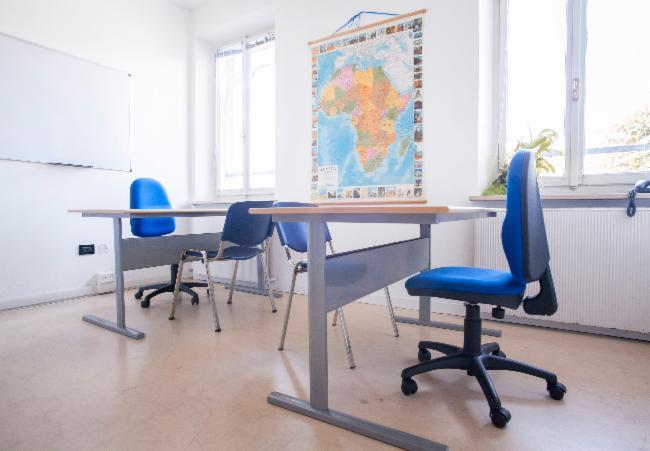 due banchi con delle sedie blu e una cartina geografica appesa al muro